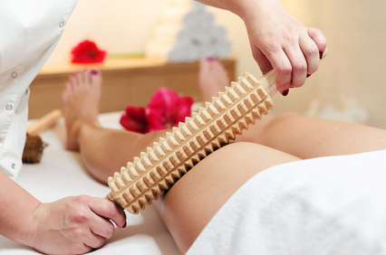 Close up of woman during spa anti cellulite massage with rolling pin or batledore